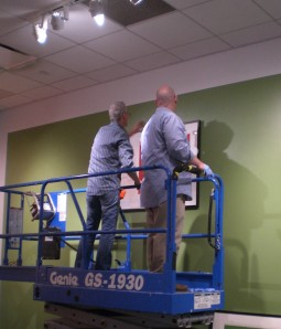 Collections and exhibitions staff on a Genie lift hanging framed artwork.