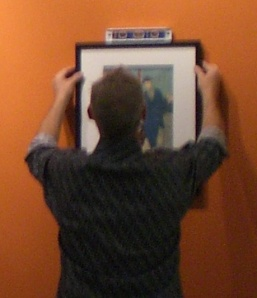staff using a level to make sure a framed work is straight.