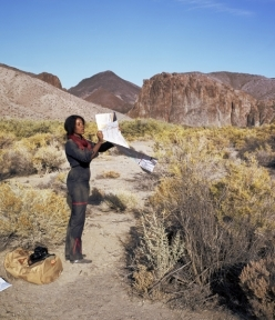Photograph of a woman standing in a desert landscape with a map