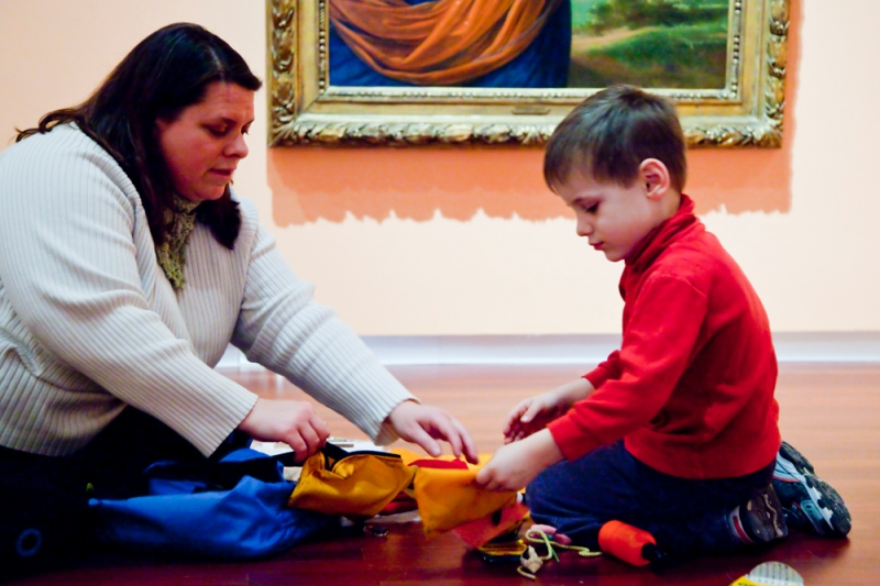 mother and son using a backpack in the museum galleries