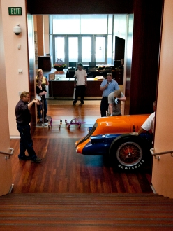 image of mormon meteor race car being rolled past the grand staircase in the UMFA galleries
