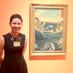 "Chelsea Thompson, Weekend Docent, smiles in front of ""The Whirlpool Naruto in Awa Province, after Hiroshige"" by an unknown artist."