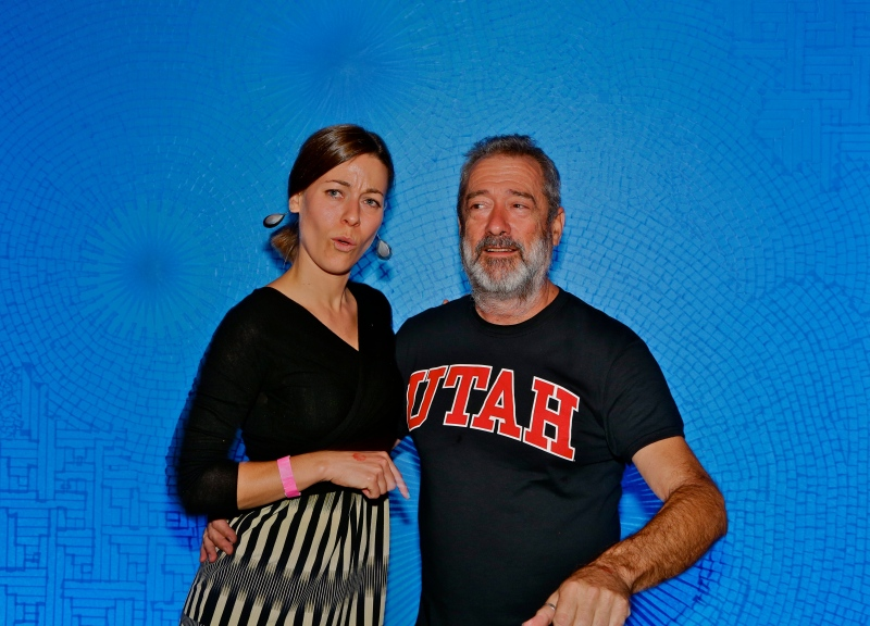 Curator Whitney Tassie and Artist Tony Feher pose in front of the window installation at the After-Hours Party.